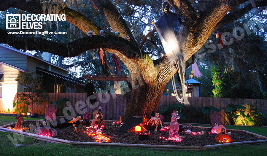 Graveyard Scene around Large Oak Tree with Hanging Ghost and skulls on a limb www.decoratingelves.com