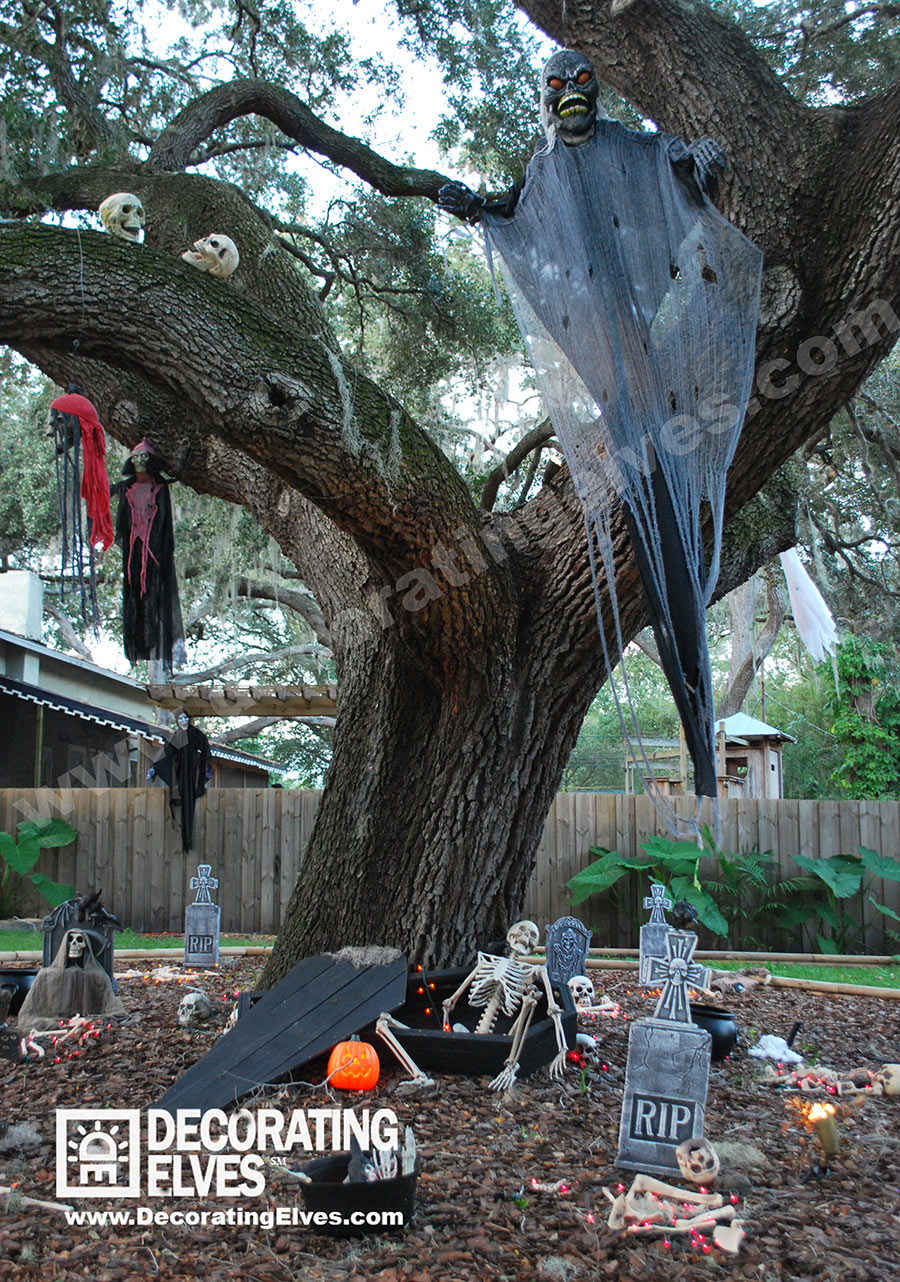 Halloween Décor Display with Hanging Ghosts and Monsters over Coffin with Tombstones & Skeletons